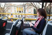 Young beautiful woman in tourist bus near Prado listens tour program in Madrid, Spain.