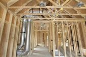 stock photo of insulator  - New Home Construction with Wood Studs Framing Heating Cooling System Air Duct Works Plumbing and Electrical Ceiling Light Cans - JPG