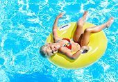 picture of one piece swimsuit  - Child  on inflatable ring in swimming pool - JPG