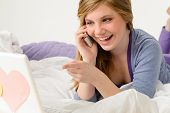 Laughing teenager relaxing by speaking on phone and using laptop