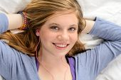 Portrait of relaxing lying young girl listening to music