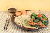 image of lo mein  - delicious chinese lo mein noodles and stir fry vegetables with cashews with chicken balls spring rolls soya sauce and chopsticks on a bamboo placemat - JPG