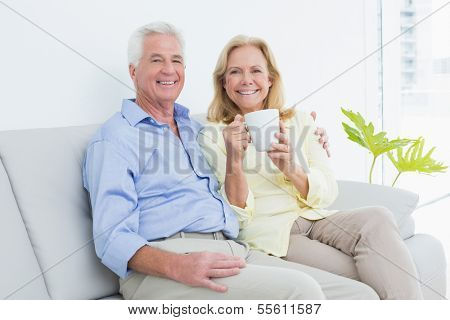 Relaxed senior couple with coffee cup sitting on sofa in a bright house