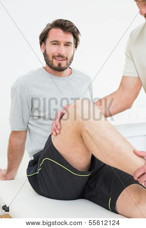 Portrait of a young man getting his knee examined at the medical office