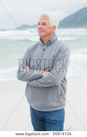Contemplative casual senior man standing with hands folded at the beach