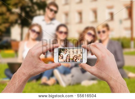 education, technology, summer holidays and teenage concept - close up of hands making picture of group of teens