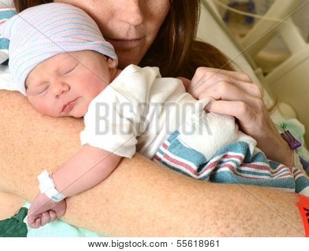 Mother Holding Newborn Infant In Hospital