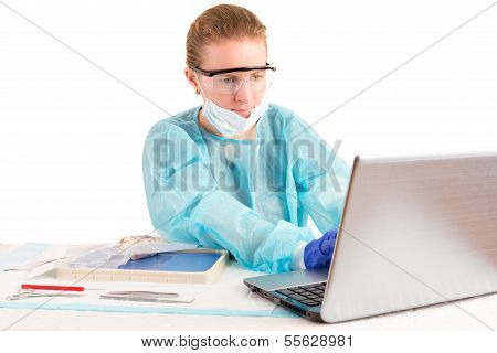 Doctor Entering Information On A Laptop Computer