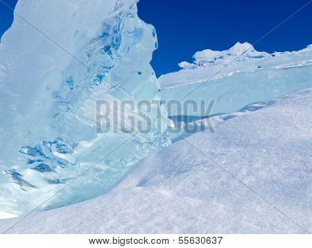 Clear Glacier Ice Chunks With Snow And Blue Sky