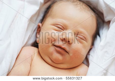 Close-up smiling newborn baby sleeping