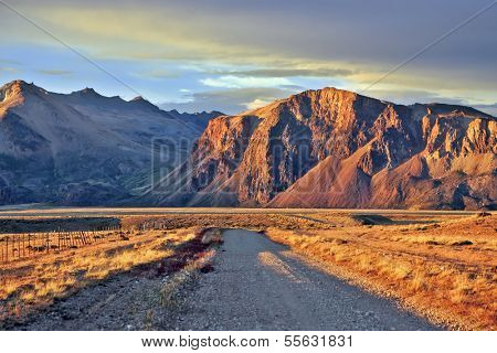Argentine Patagonia. The magnificent Perito Moreno National Park. The gravel road between the endless pampas. Sunset illuminates the mountains and steppe red sun