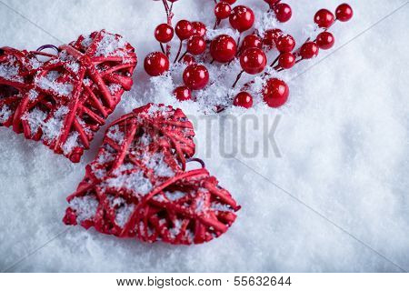 Two beautiful romantic vintage red hearts with mistletoe berries on a white snow background. Christmas, love and St. Valentines Day concept.