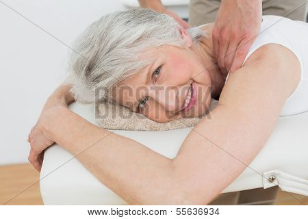 Male physiotherapist massaging a senior woman's shoulder in the medical office