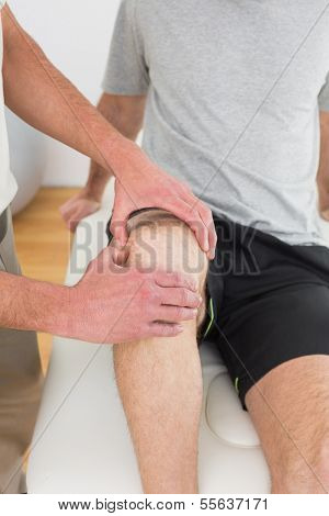 Close-up mid section of a young man getting his knee examined at the medical office