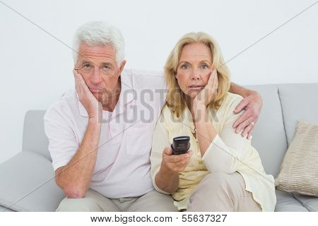 Relaxed shocked senior couple watching television in a house