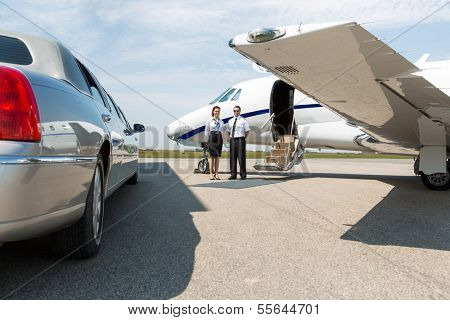 Airhostess and pilot standing neat limousine and private jet at airport terminal