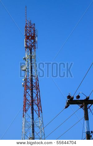 Telecommunication mast with microwave link and TV transmitter antennas over a blue sky