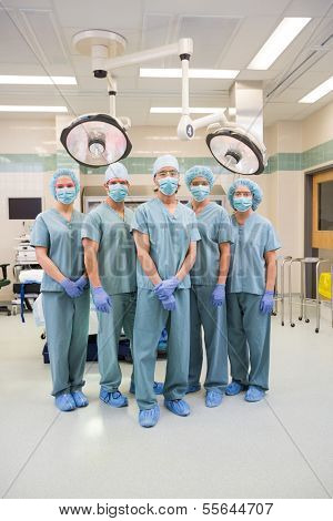 Full length portrait of surgical team in scrubs standing inside operation room