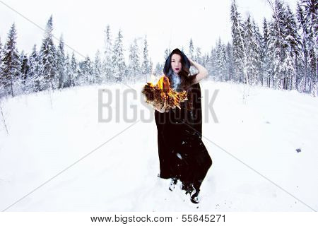 Witch or woman in black cloak with fire ball in white snow forest