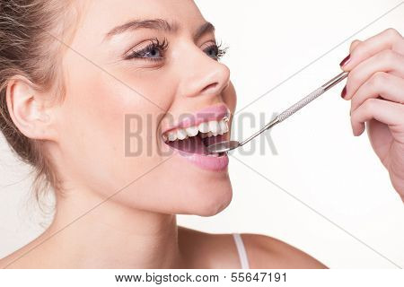 Attractive woman with beautiful white teeth holding a small dental mirror in her mouth to display her teeth
