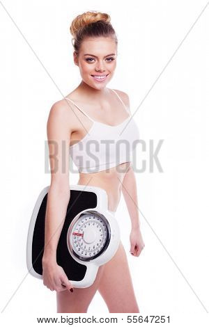 Slim, attractive blonde woman, dress in plain white underwear, carries a set of bathroom scale. Maintaining an optimum weight concept.