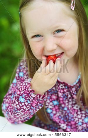 Smiling Little Girl Eating A Strawberry.