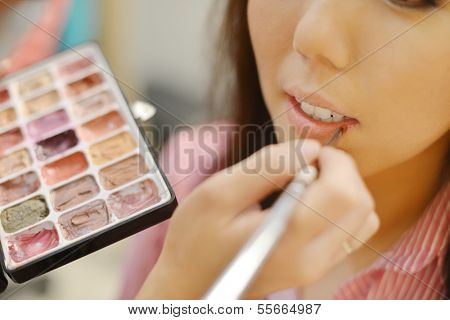 Young beautiful Asian bride applying wedding make-up by make-up artist. Focus on lips.
