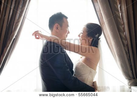 Romantic Asian Chinese wedding couple. Bride and groom dancing on wedding day.