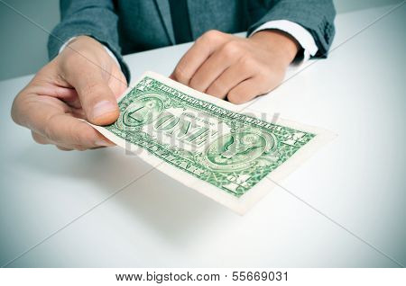 a man wearing a suit sitting in a desk offering a one US dollar bill