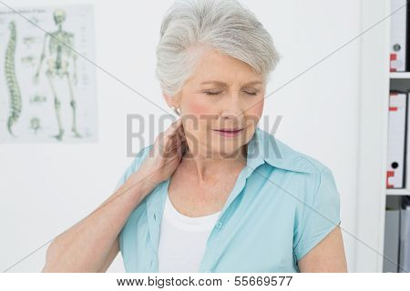 Senior woman suffering from neck pain with eyes closed in the medical office