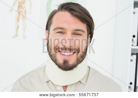 Portrait of a smiling young man wearing surgical collar in the medical office