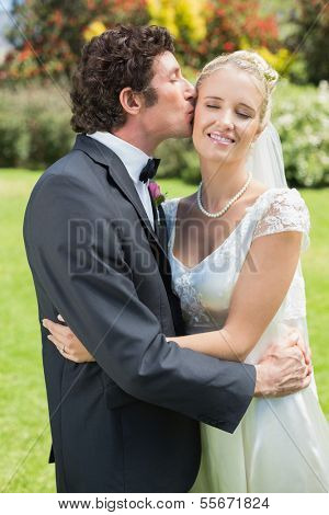 Groom kissing his pretty new wife on the cheek in the countryside