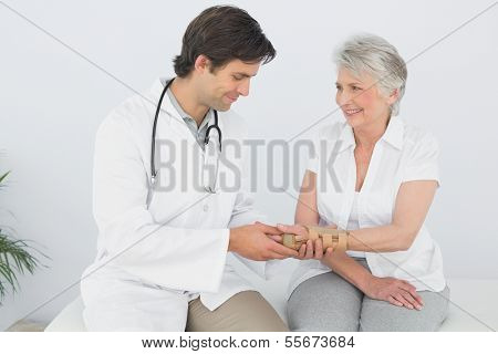 Male physiotherapist examining a senior woman's wrist in the medical office