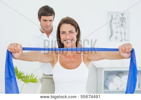 Male therapist assisting young woman with exercises in the medical office