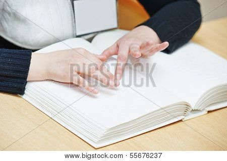 Blind or visually handicapped woman hands reading book written in Braille