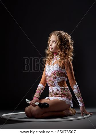Beautiful young gymnast posing with mace and hoop