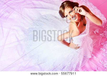 Beautiful charming bride in a luxurious dress looking up. Over pink background.