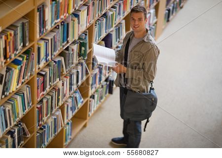 Student holding a book from shelf in library smiling at camera at the university