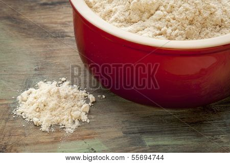 gluten free coconut flour in a red stoneware bowl and spilled on a wooden cutting board