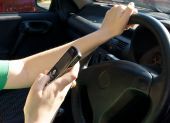 stock photo of driving  - Woman driving while making a text message - JPG