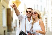 summer holidays, dating, city break and tourism concept - couple with camera and travellers guide poster