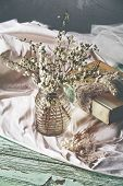 pic of keepsake  - Spring white flower branches on grunge table with silk cloth and a book with lace and pearl wedding keepsakes - JPG