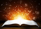 Old open book with magic light and falling stars on wooden table