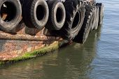 stock photo of yanks  - old tires serve as bumpers for a tug boat - JPG