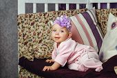 picture of babygro  - Little girl with bow on her head sitting on couch - JPG