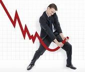 picture of stock market crash  - Businessman trying to change the down going profits of the company - JPG