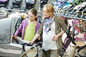 stock photo of buggy  - Young pregnant woman choosing baby carriage or pram buggy for newborn at shop store - JPG
