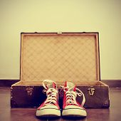 stock photo of nostalgic  - a pair of red sneakers in front of an open old brown suitcase with a retro effect - JPG