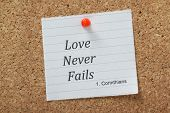 stock photo of bible verses  - The phrase Love Never Fails taken from First Corinthians in the christian Holy Bible on a piece of note paper pinned to a cork notice board - JPG