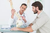 stock photo of vertebrae  - Male doctor explaining the spine to a patient in medical office - JPG